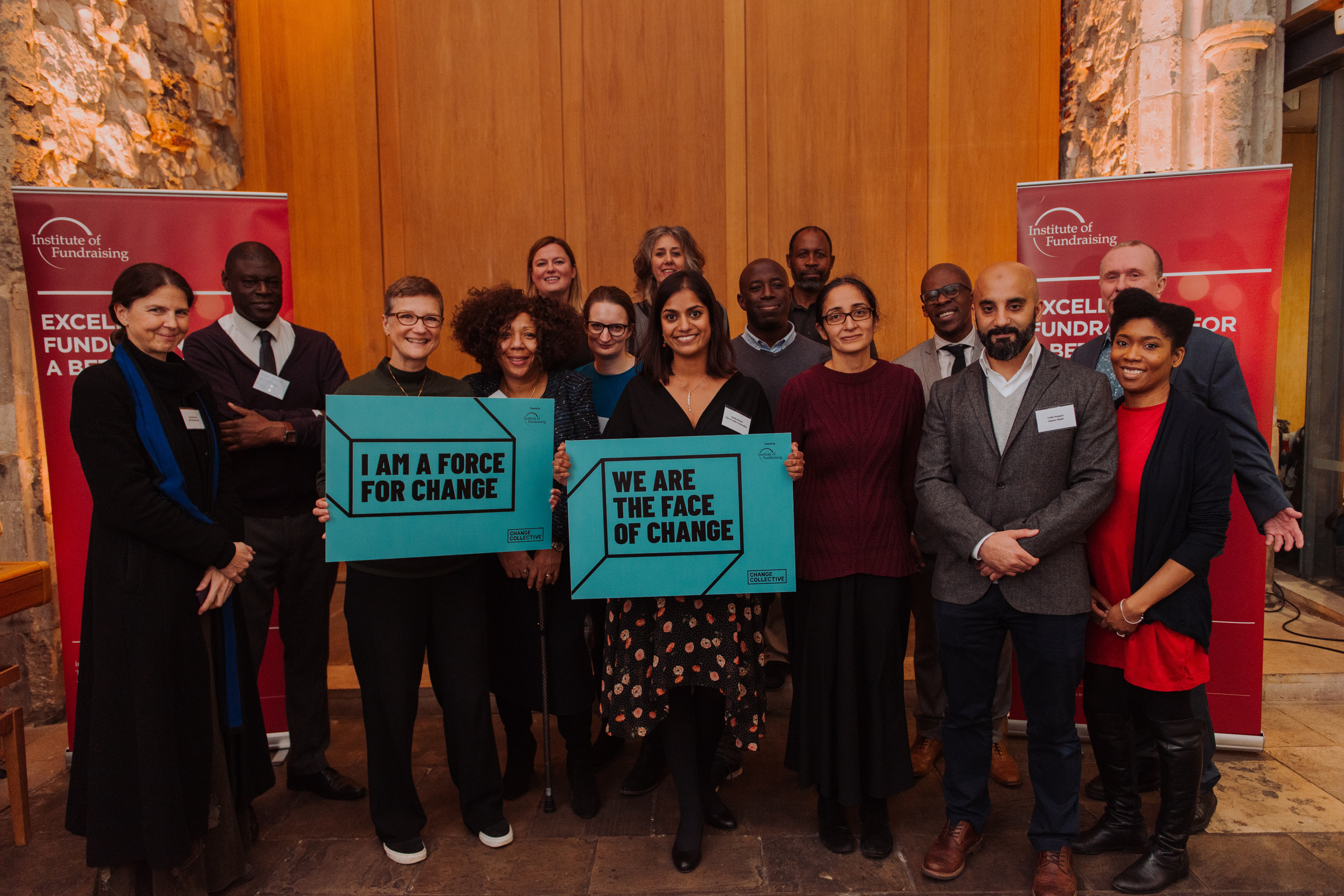 A diverse group of fundraisers together. One is holding a board with the words I am a force for change and another holding a board saying we are the face of change.