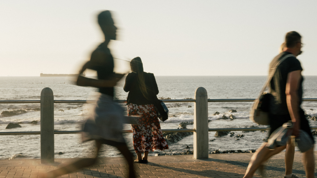 Person standing looking at the sea while runners and people walking are in the front of the photo