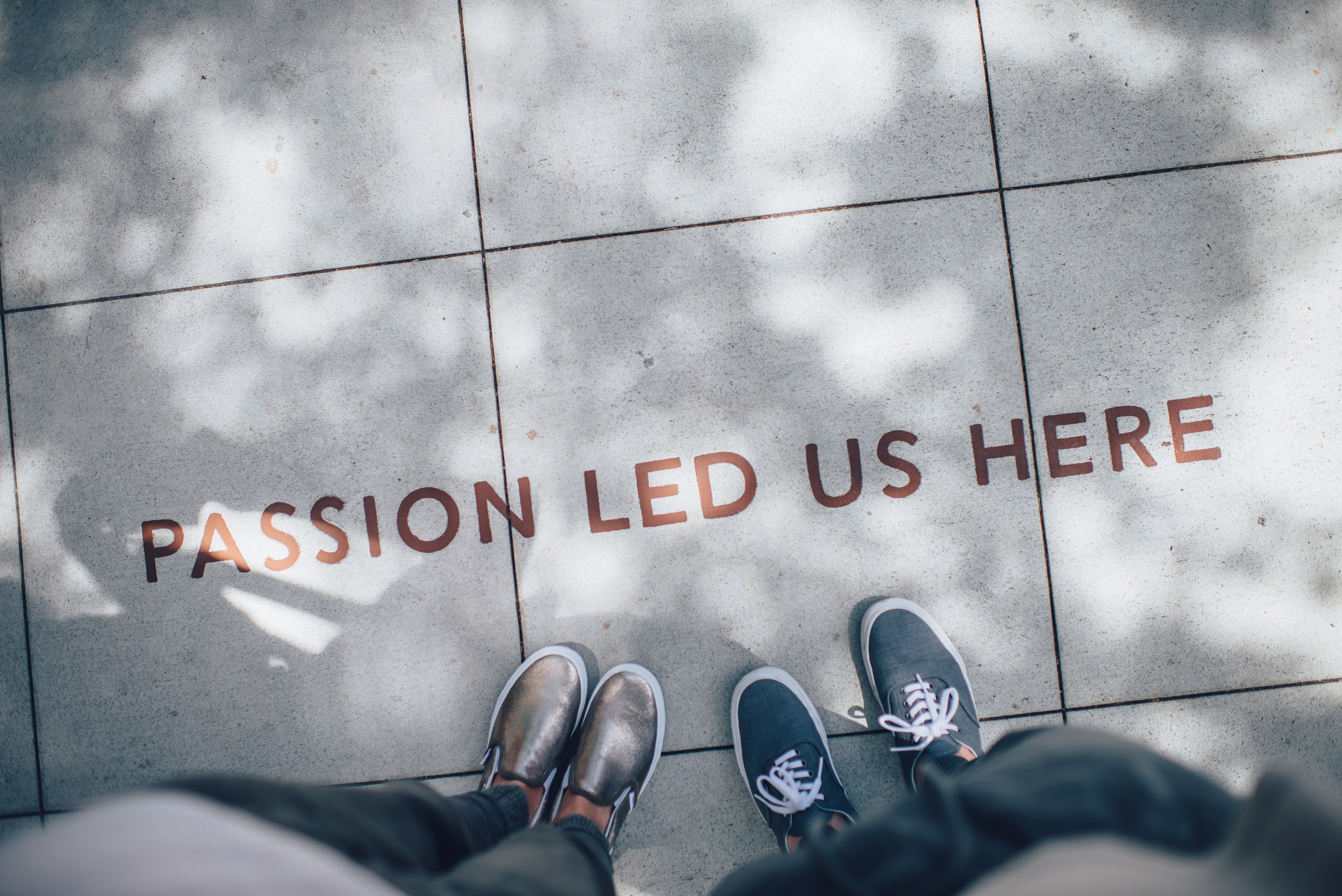 Two pairs of feet visible in front of a sign on the floor saying passion led us here.