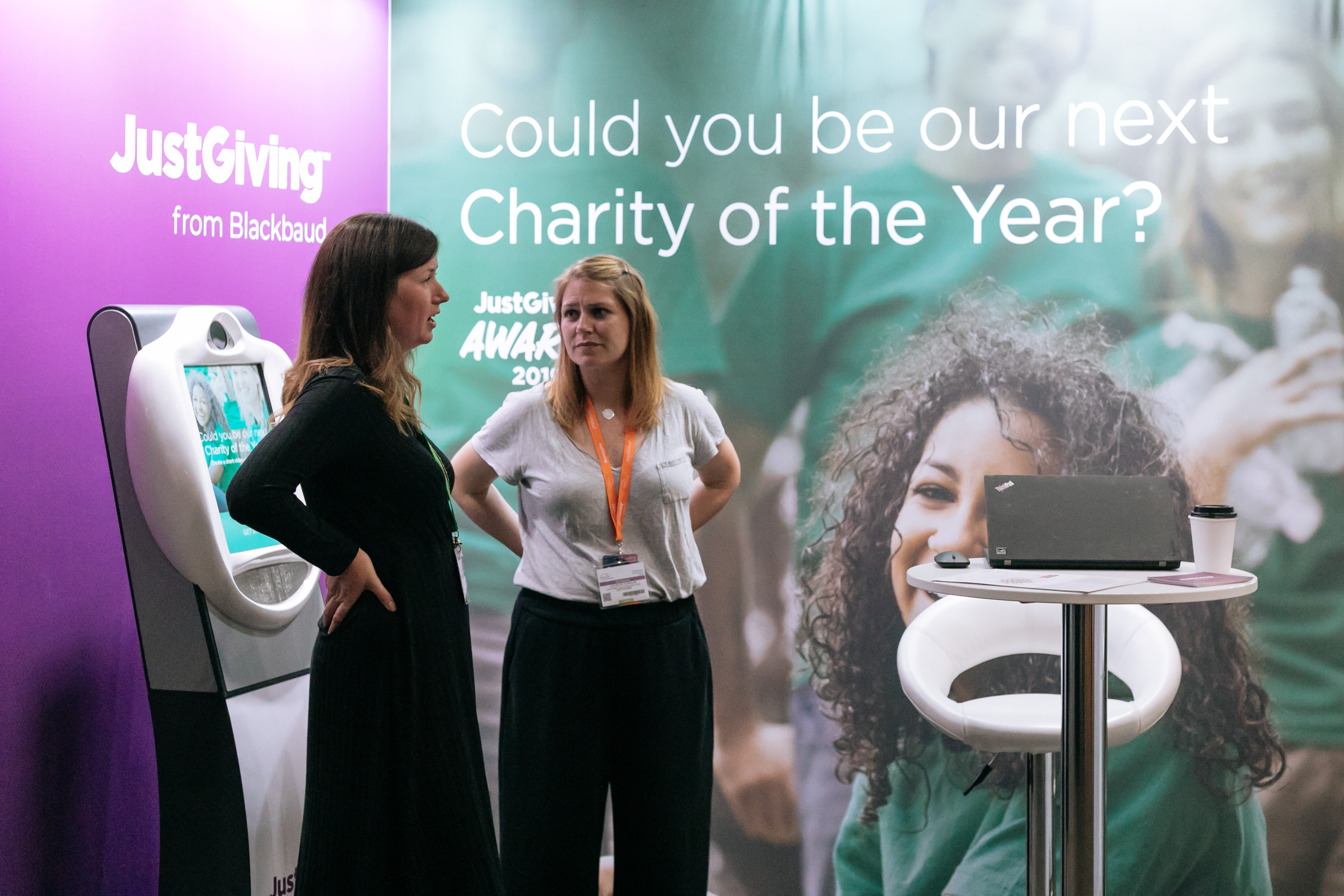 JustGiving exhibition stand with two people standing in front of the banners talking with hands behind their backs.